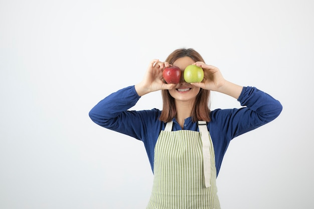 Młoda dziewczyna trzyma zielone i czerwone jabłka przed jej oczami.