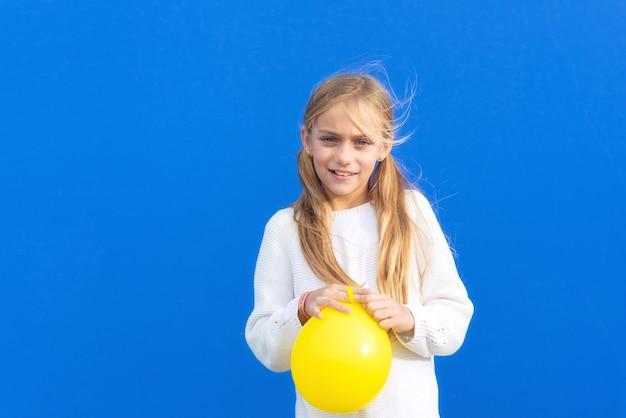 Młoda dziewczyna trzyma żółty balon