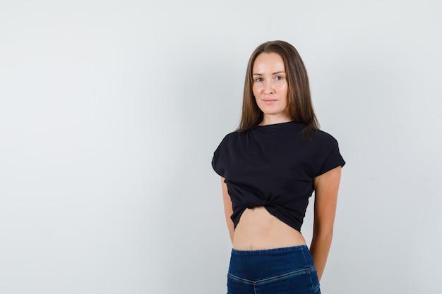 Młoda dziewczyna trzymając się za ręce na plecach w czarną bluzkę, spodnie i wesoły wyglądający
