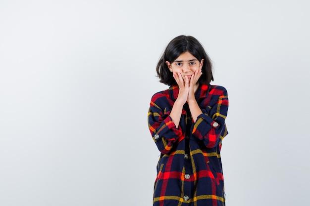 Młoda dziewczyna trzymając się za ręce na policzkach w kraciastej koszuli i patrząc nieśmiało. przedni widok.
