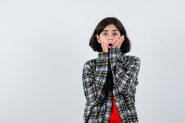 Młoda dziewczyna trzymając się za ręce przy ustach w kraciastej koszuli i czerwonej koszulce i patrząc zaskoczony, widok z przodu.