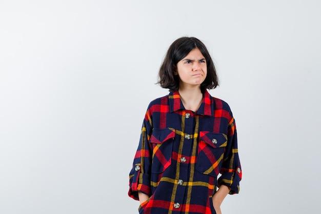 Młoda dziewczyna trzymając się za ręce w kieszeni w kraciastej koszuli i patrząc zirytowany. przedni widok.