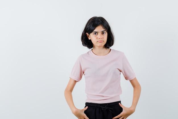 Młoda dziewczyna trzymając się za ręce w talii w różowej koszulce i czarnych spodniach i wygląda uroczo