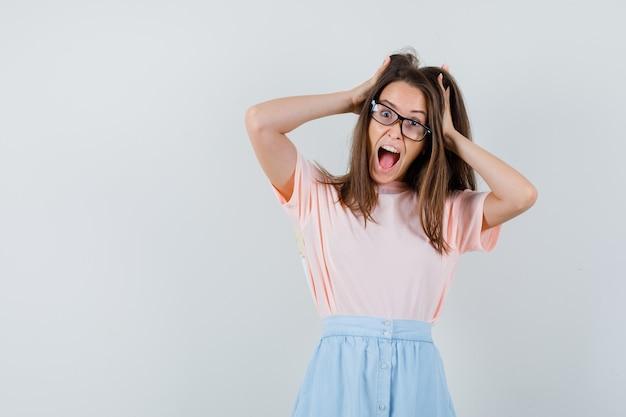 Młoda dziewczyna trzymając się za ręce we włosach w t-shirt, spódnica i szalony, widok z przodu.