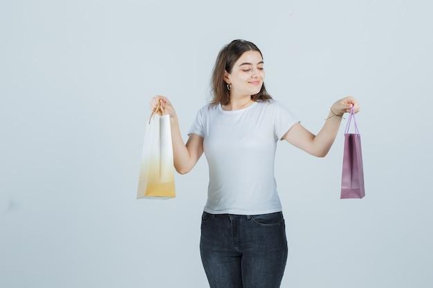 Młoda dziewczyna, trzymając torby na prezenty w t-shirt, dżinsy i patrząc zadowolony, widok z przodu.