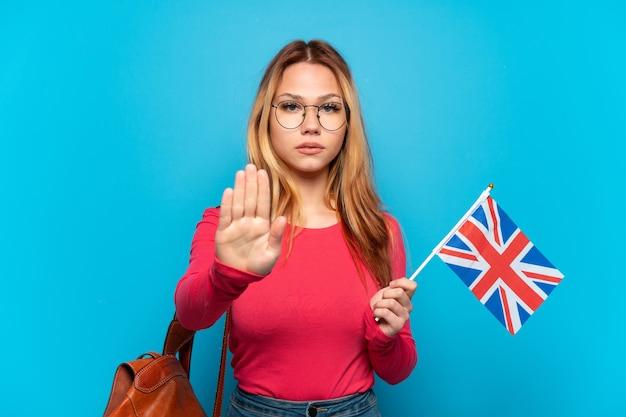 Młoda dziewczyna trzymająca flagę wielkiej brytanii na odosobnionym niebieskim tle wykonująca gest zatrzymania stop