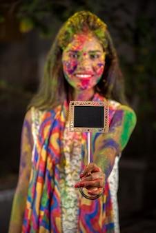 Młoda dziewczyna trzymająca małą tabliczkę z okazji festiwalu holi z twarzami pomalowanymi na pudrowe kolory, z kolorowym pluskiem.