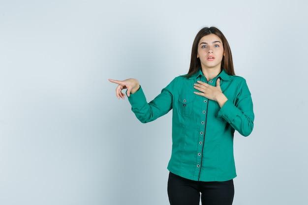 Młoda dziewczyna trzymająca rękę na piersi, wskazująca w lewo z palcem wskazującym w zielonej bluzce, czarnych spodniach i wyglądająca na zszokowaną. przedni widok.