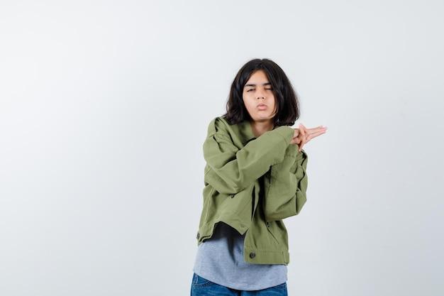 Młoda dziewczyna trzymająca się za ręce, zamykająca oczy w szarym swetrze, kurtce khaki, spodniach dżinsowych i wyglądająca na zmęczoną, widok z przodu.