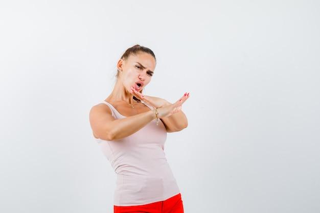 Młoda dziewczyna trzymająca skrzyżowane ręce, pokazująca brak znaku w beżowym topie i czerwonych spodniach, wyglądająca na pewną siebie. przedni widok.