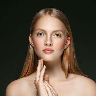 Młoda dziewczyna twarz uroda skóry portret z długie blond włosy z ręką na ciemnym tle. strzał studio.