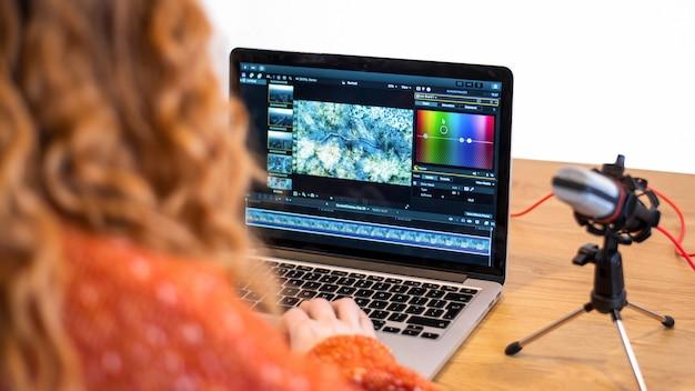 Młoda dziewczyna twórca treści edytuje wideo na swoim laptopie. mikrofon i słuchawki na stole. praca z domu