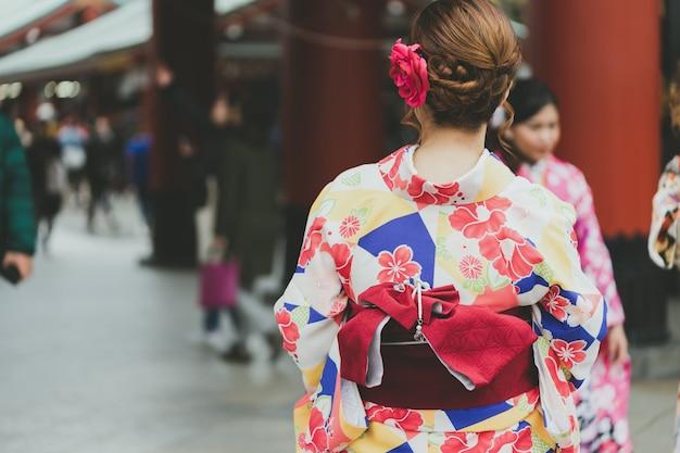 Młoda dziewczyna ubrana w japońskie kimono stojące przed świątynią sensoji w tokio,