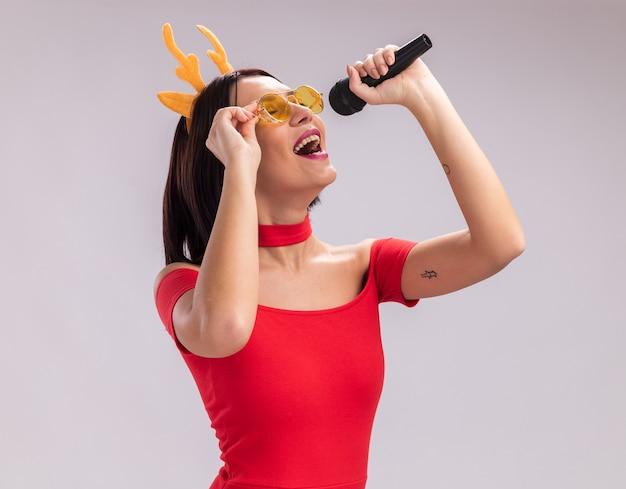 Młoda dziewczyna ubrana w opaskę z poroża renifera i okulary trzymające mikrofon, chwytające okulary śpiewające z zamkniętymi oczami na białym tle