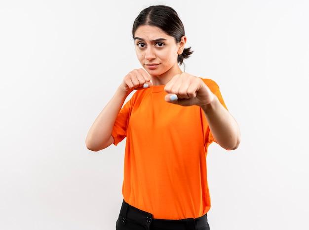 Młoda dziewczyna ubrana w pomarańczową koszulkę z zaciśniętą pięścią pozuje jak bokser stojący na białej ścianie