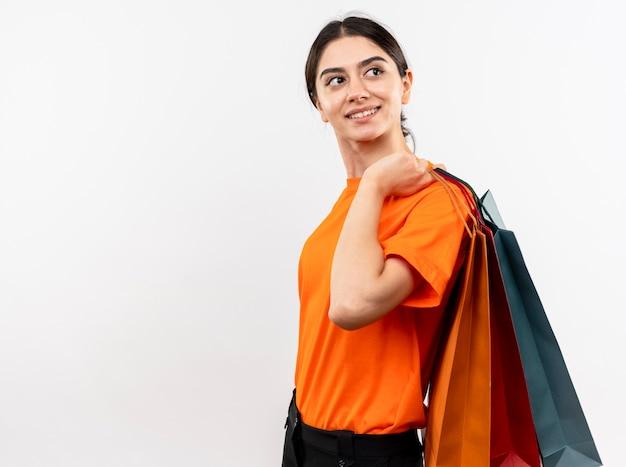 Młoda dziewczyna ubrana w pomarańczowy t-shirt trzymając papierowe torby patrząc na bok z szczęśliwą twarzą uśmiechniętą wesoło stojąc na białej ścianie