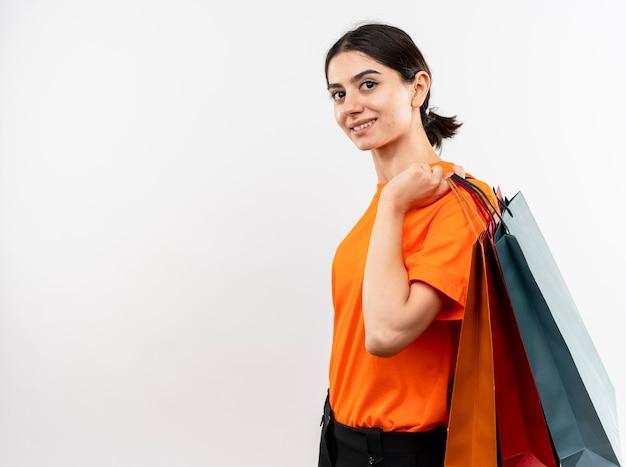 Młoda dziewczyna ubrana w pomarańczowy t-shirt trzymając papierowe torby patrząc na kamery z hapy uśmiechniętą twarz wesoło stojąc na białym tle