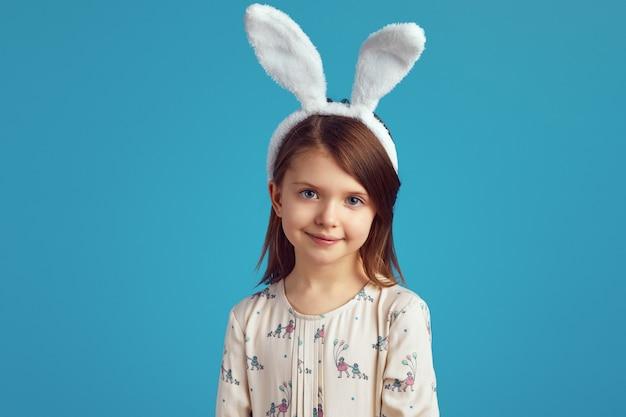 Młoda dziewczyna ubrana w uszy królika i uśmiechnięta na niebieskiej ścianie