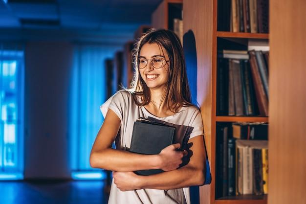 Młoda dziewczyna uczeń z szkłami w bibliotece stoi blisko półka na książki. dziewczyna uśmiecha się i trzyma w rękach książkę. przygotowanie do egzaminu