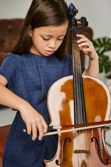 Młoda dziewczyna uczy się gry na wiolonczeli w domu