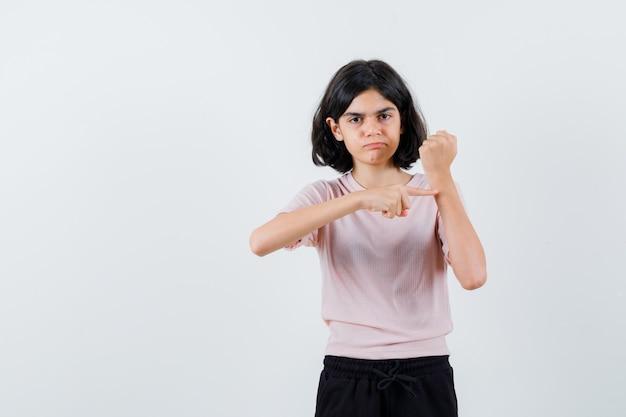 Młoda dziewczyna udaje, że wskazuje zegar w różowej koszulce i czarnych spodniach i wygląda uroczo