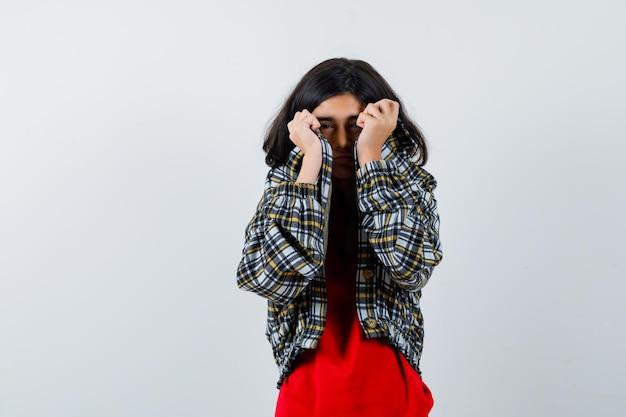 Młoda dziewczyna ukrywa się w kraciastą koszulę i czerwoną koszulkę i wygląda poważnie. przedni widok.