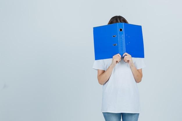 Młoda dziewczyna ukrywa twarz za folderem w białej koszulce i patrząc przygnębiony, widok z przodu.