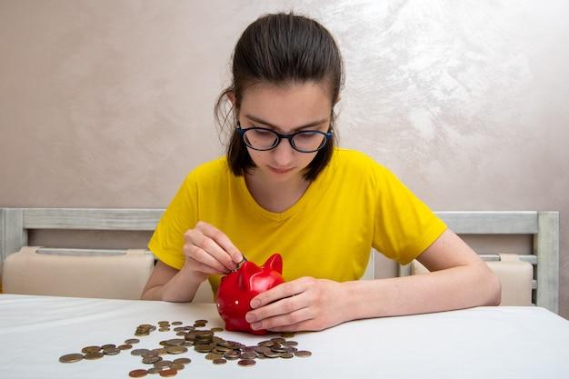Młoda dziewczyna umieścić monety pieniędzy w czerwonej skarbonce, aby zaoszczędzić pieniądze, kilka monet na stole.