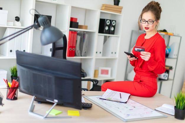 Młoda dziewczyna usiadła na stole w biurze i trzymała w rękach kartę kredytową i telefon.