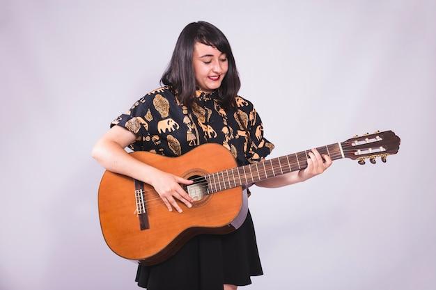 Młoda dziewczyna uśmiecha się i stwarzających z gitarą