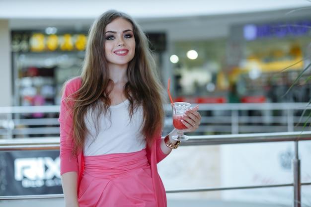 Młoda dziewczyna uśmiecha się z napojem w dłoni