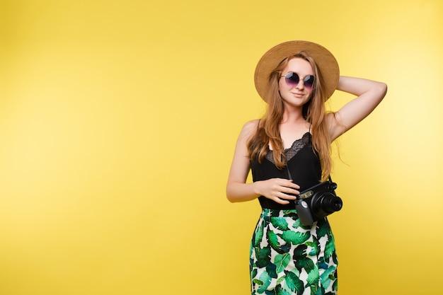 Młoda dziewczyna utrzymuje kamerę w słomianym kapeluszu i szkłach