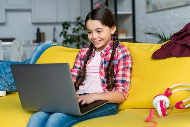 Młoda dziewczyna używa laptop indoors