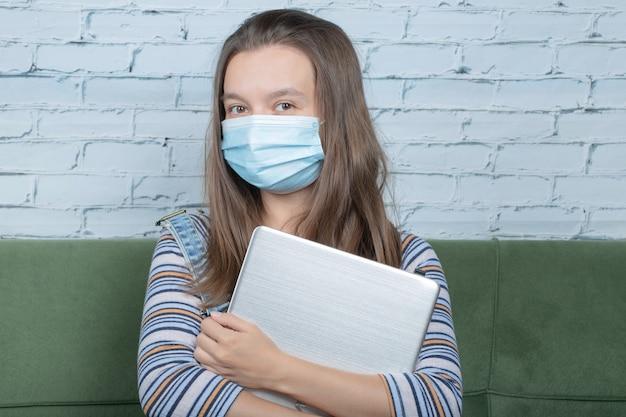 Młoda dziewczyna używa profilaktycznej maski na twarz podczas korzystania z technologii w biurze