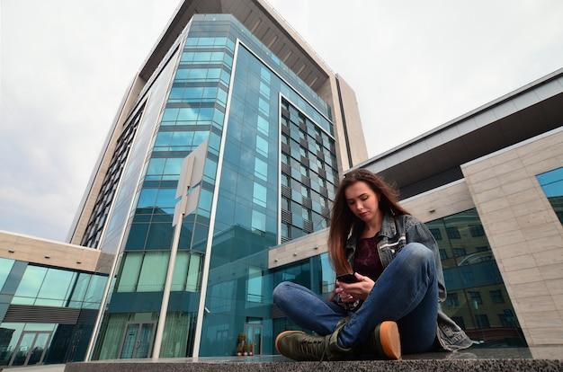 Młoda dziewczyna używa smartphone na budynku biurowym