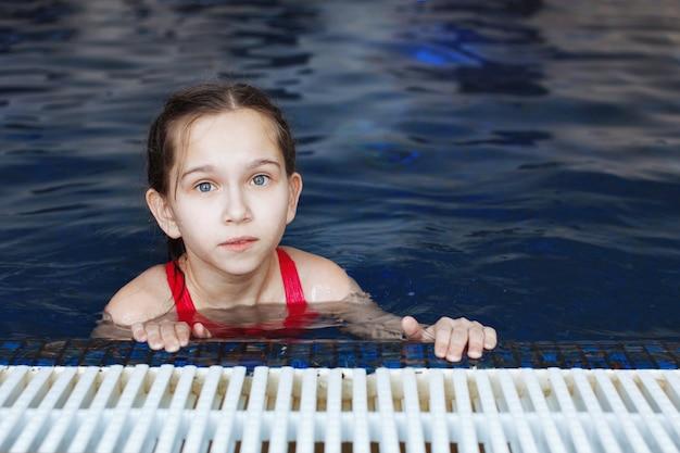 Młoda dziewczyna w basenie z niebieską wodą, patrzy w kamerę