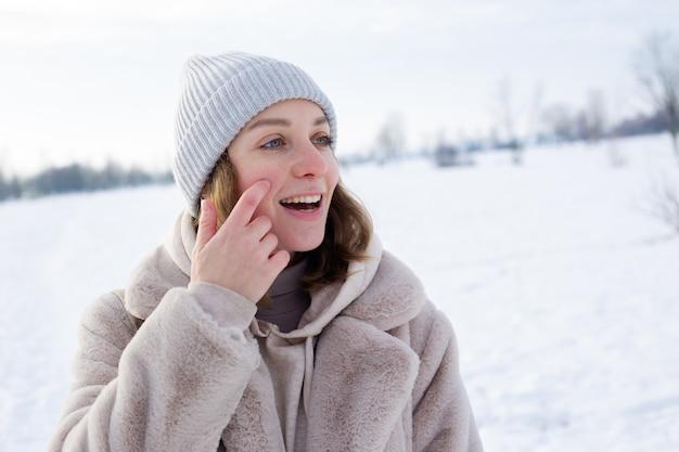 Młoda dziewczyna w beżowym futrze ze sztucznego futra spaceruje zimą
