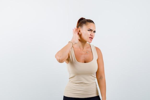 Młoda dziewczyna w beżowym topie, czarnych spodniach trzyma się za ręce przy uchu, by coś usłyszeć i patrzy na skupiony widok z przodu.