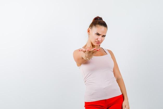 Młoda dziewczyna w beżowym topie i czerwonych spodniach, rozciągając rękę