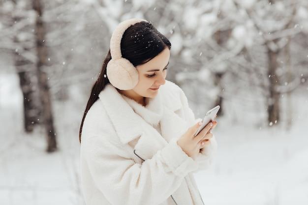 Młoda dziewczyna w białe zimowe ubrania i puszyste słuchawki trzymając telefon w śnieżnym czasie.