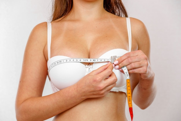 Młoda dziewczyna w białej bieliźnie mierzy swoje piersi metrem.