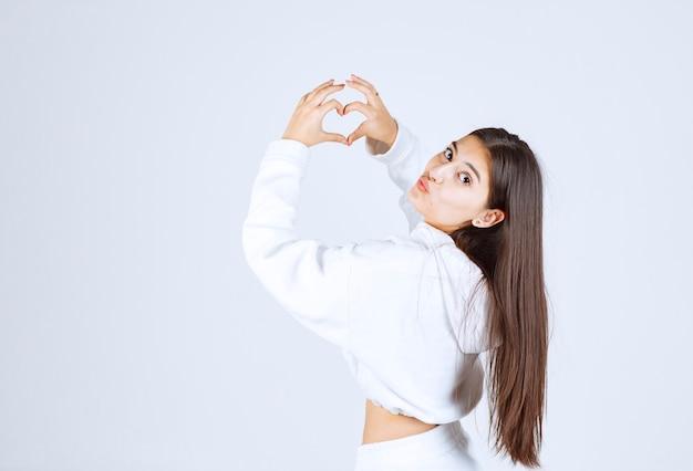 Młoda dziewczyna w białej bluzie z kapturem pokazując serce dwiema rękami.