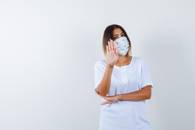 Młoda dziewczyna w białej koszulce i masce pokazuje znak stopu, trzymając rękę pod łokciem i patrząc pewnie, widok z przodu.