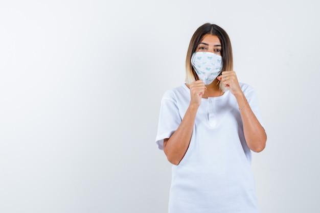 Młoda dziewczyna w białej koszulce i masce stojącej w pozie walki i patrząc pewnie, widok z przodu.