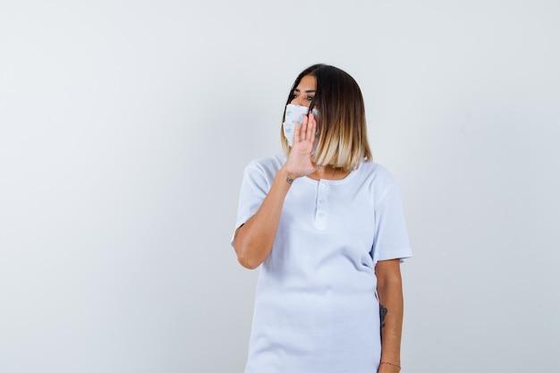 Młoda dziewczyna w białej koszulce, maska pokazująca znak stopu, odwracająca wzrok i wyglądająca poważnie, widok z przodu.