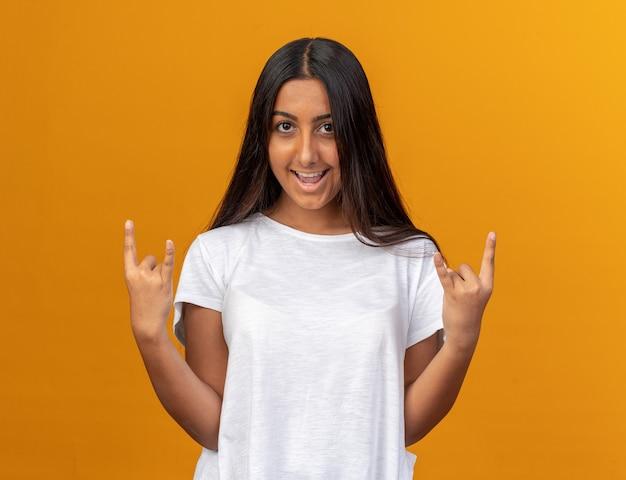 Młoda dziewczyna w białej koszulce patrząc na kamery szczęśliwy i wesoły pokazujący symbol rocka