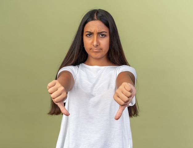 Młoda dziewczyna w białej koszulce patrząca na aparat jest niezadowolona pokazując kciuk w dół stojący nad zielenią