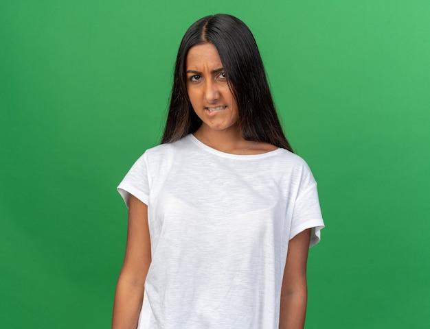 Młoda dziewczyna w białej koszulce patrząca na kamerę robiąca krzywe usta z rozczarowanym wyrazem twarzy