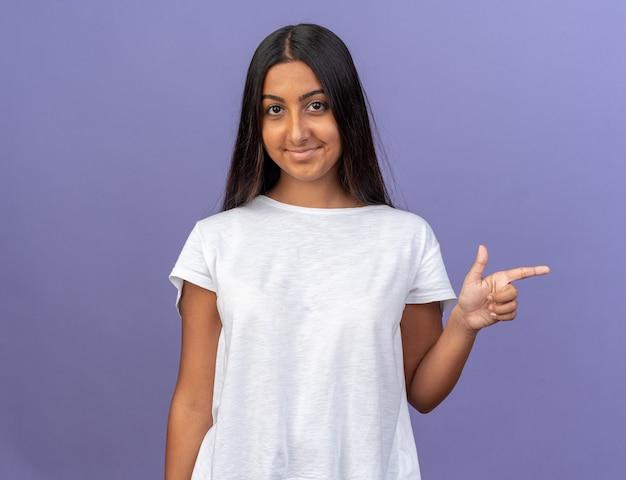 Młoda dziewczyna w białej koszulce patrząca w kamerę z uśmiechem na zadowolonej twarzy wskazująca palcem wskazującym w bok, stojąca na niebiesko