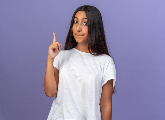 Młoda dziewczyna w białej koszulce patrząca w kamerę zdezorientowana, wskazując palcem wskazującym w górę, stojąc nad niebieskim
